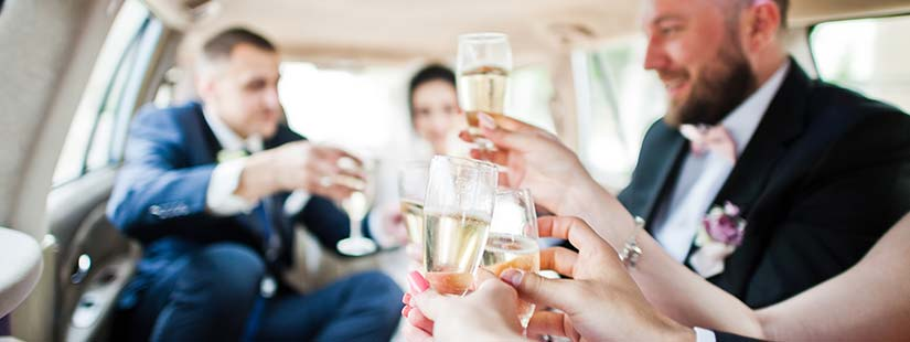 Wedding Party toasting champagne in Limo