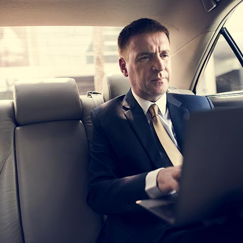 Businessman Working in back of Limo